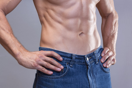 ombligo: Primer plano de raza caucásica hombre sin camisa de uniforme azul jeans con hermosos músculos abdominales chisled magras sobre fondo gris Foto de archivo