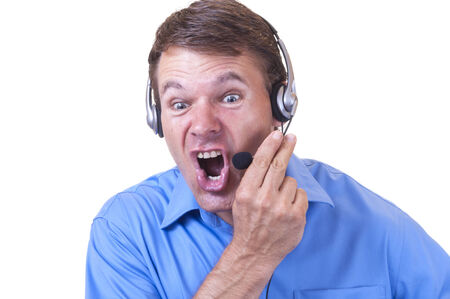 collared shirt: Hot tempered angry Caucasian man wearing blue collared shirt and communications headset holds mic and yells furiously on white background