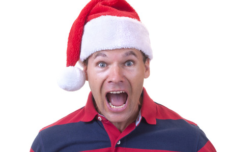 disbelief: Stressed out Caucasian man wearing red Santa hat screams in disbelief on white background Stock Photo
