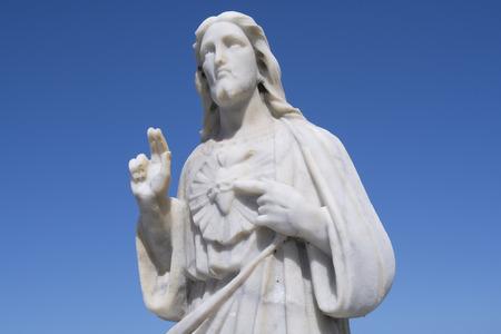 sacre coeur: Haute statue en marbre de la moitié du Sacré-C?ur de Jésus pointant à c?ur et levant deux doigts sur fond de ciel bleu clair Banque d'images