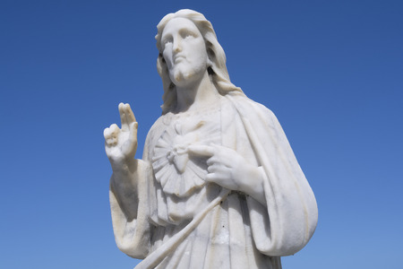 sacred heart: Upper half marble statue of Sacred Heart of Jesus pointing to heart and holding up  two fingers on clear blue sky background