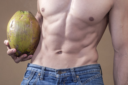 Closeup of man with lean abdominals wearing blue jeans and holding whole raw coconut next to waist Stock Photo
