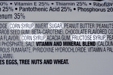 Closeup of ingredients list of granola health bar with forms of sugar highlighted