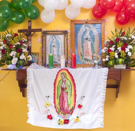 Prachtig versierd altaar met bloemen, religieuze voorwerpen en ballonnen in Mexicaanse vlag kleuren om de verschijning van Onze Lieve Vrouw van Guadalupe herdenken Stockfoto