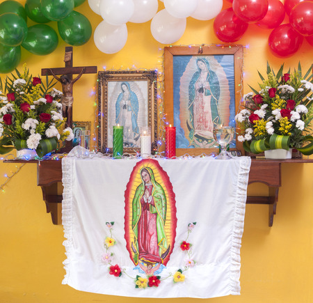 Beautifully decorated altar with flowers, religious objects and balloons in Mexican flag colors to commemorate the apparition of Our Lady of Guadalupe