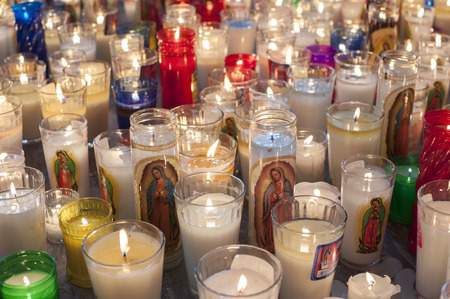 our: Hundreds of glass vase religious candles featuring the Virgin Mary as Our Lady of Guadalupe lit on church floor in Mexico