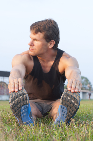 hamstring: Focus on shoes as muscular Caucasian man sits in grass reaching for toes to do hamstring stretch on grass sport field