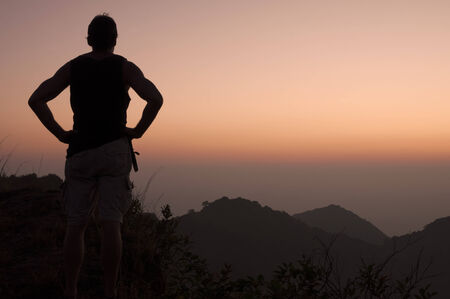 man looking out: Silhouette of explorer man standing on top of mountain with hands on hips looking out at orange sunset sky with copy space Stock Photo