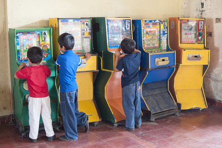 arcades: PICHUCALCO, CHIAPAS, MEXICO - DECEMBER 21, 2014: Three young boys entertain themselves by playing old Mexican bingo arcade games at the bus terrminal in Pichucalco