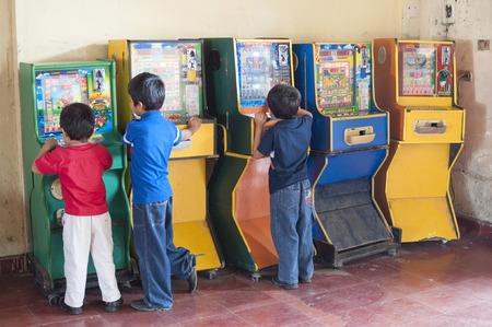 arcade games: PICHUCALCO, CHIAPAS, MEXICO - DECEMBER 21, 2014: Three young boys entertain themselves by playing old Mexican bingo arcade games at the bus terrminal in Pichucalco