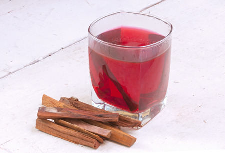 logwood: Small stack of pieces and glass of red tea of Haematoxylum brasiletto Mexican logwood on white table Stock Photo