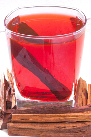 logwood: Closeup of wood pieces and glass of red tinted Haematoxylum brasiletto Mexican logwood tea on white table
