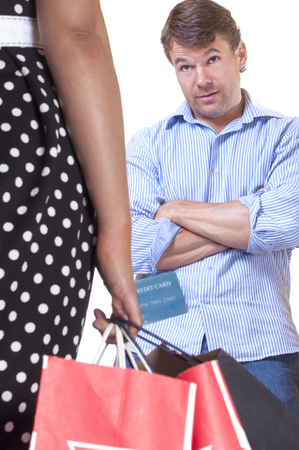 Caucasian man with arms crossed looks with raised eyebrows at wife carrying shopping bags and credit card in hand and waits for explanation on white background