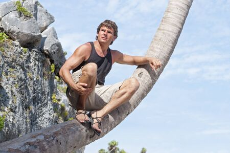 sandals: Handsome muscular Caucasian man in shorts and sandals sits on leaning coconut palm tree under sunny sky to view the scenery