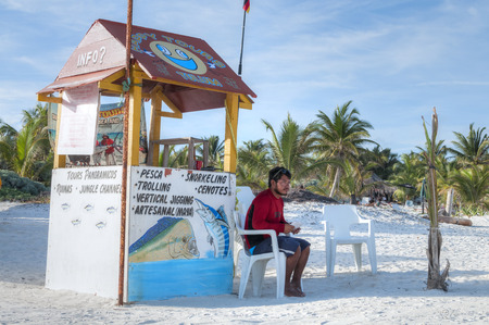 roo: TULUM, MEXICO - JANUARY 23, 2015: A local fisherman sits at a kiosk on a white sand beach offering fishing tours to catch local gamefish in Tulum, Mexico