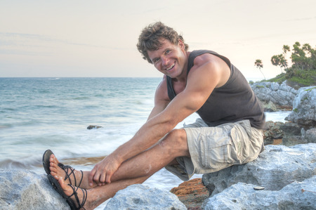 wearing sandals: Handsome muscular Caucasian man with happy smile as he sits on rocky Caribbean seashore stretching his legs wearing sandals, shorts and tank top