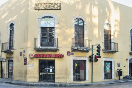 merida: MERIDA, MEXICO - JANUARY 19, 2015: A Burger King restaurant occupies an old rustic colonial style building in on a street corner in downtown Merida, Yucatan