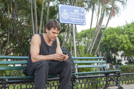 merida: MERIDA, MEXICO - JANUARY 19, 2015: Wireless Wifi service is now available in many of the town squares and parks of Mexico.  A foreign traveler uses the free Wifi in the park in Merida, Yucatan.