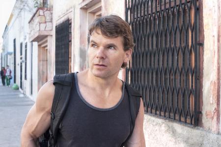 merida: Handsome Caucasian man wearing black tank top and backpack walks down sidewalk in colonial city of Merida, Mexico Stock Photo