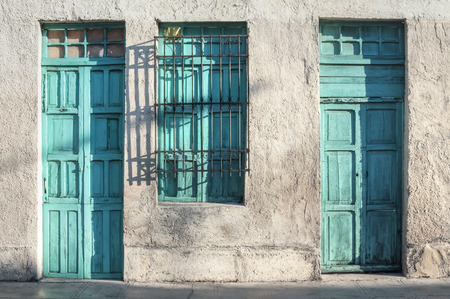 merida: Two aqua green painted wooden doors and window of rustic exterior of old colonial style building illuminated by morning light in Merida, Yucatan, Mexico
