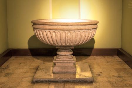 Pila bautismal de piedra iluminada en la Catedral de Ildefonso en Mérida, México Foto de archivo