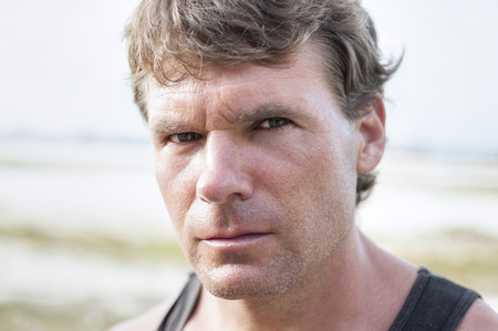Closeup portrait of rugged Caucasian man with stern bold facial expression, distinct features, and intense predator eyes in undefined outdoor environment