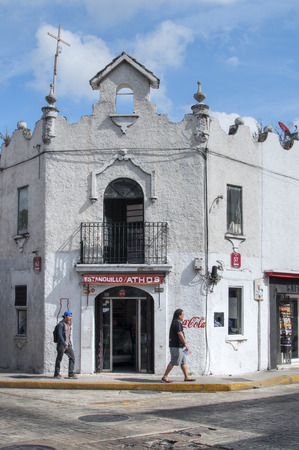 merida: MERIDA, MEXICO - JANUARY 19, 2015: Tourists walk along sidewalk in front of old colonial style building on corner of streets 57 and 62 in Merida, Yucatan