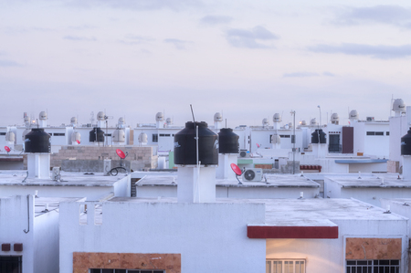 merida: MERIDA, MEXICO - JANUARY 20, 2015: Water tanks sit on the rooftops of homes in a recently developed urban area of Merida, Yucatan