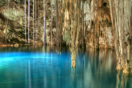 cave exploring: Beautiful clear blue water of Xkenken cenote in Dzitnup, Mexico illuminated from above with tree roots and stalactites hanging from ceiling of cavern Stock Photo