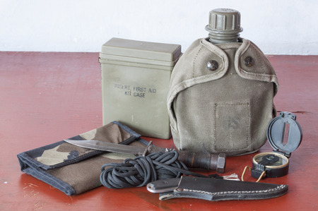 Assortment of survival hiking gear including first aid kit, canteen, knife, parachute cord, compass and map holder on old wood table
