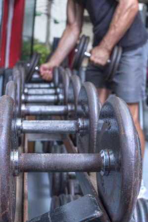 unrecognized: Focus on rusty dumbbell weight on rack in foreground while unrecognized man in background picks up dumbbells in gym Stock Photo