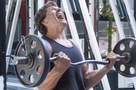 Muscular Caucasian man in tank top painfully struggles to complete repetition of arm curls in gym