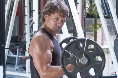 tank top: Muscular Caucasian man wearing tank top curls heavy weights in gym while looking at camera