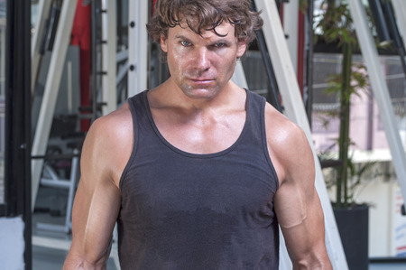 Muscular sweaty Caucasian man with intense expression looking at camera and wearing tank top in gym