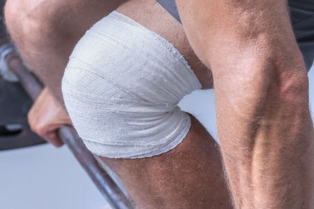 attempting: Closeup of mans knee wrapped in sport bandage while attempting to lift heavy weights on barbell in gym