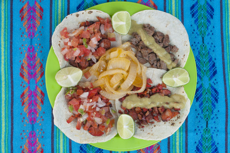 high angle shot: High angle shot of taco plate display of four corn tortillas with different kinds of barbecued meat, salsa, limes and onion on a decorative blue tablecloth