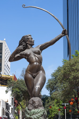 paseo: MEXICO CITY, MEXICO - MARCH 5, 2015: Beautiful bronze statue of Diana the Hunter portraying a woman posing with hunting bow is publicly displayed near Paseo de la Reforma in downtown Mexico City, Mexico