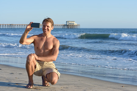 Handsome shirtless Caucasian man kneeling on sand at beach with pier in background smiles and takes selfie photo