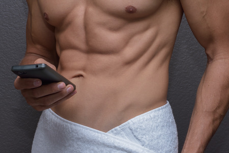 and the horizontal man: Closeup of abs and chest of sexy muscular Caucasian man with white towel around waist holding cell phone in one hand as he texts or dials Stock Photo