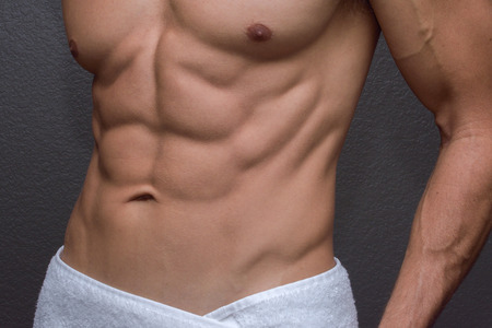shirtless man: Closeup of sexy torso showing muscular lean abdominals and chest of tan Caucasian man with white towel wrapped around waist next to textured gray wall background