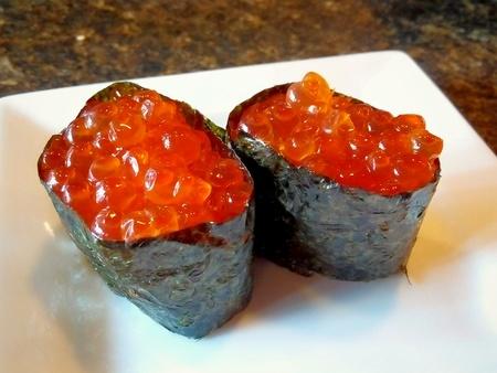 Twee ikura zalmkuiten sushi gewikkeld in zeewier en geserveerd op een witte plaat Stockfoto