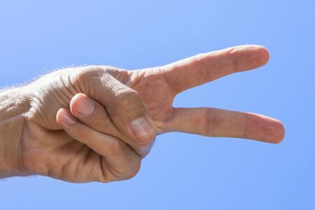 Closeup low angle of male hand showing peace sign with blue sky background on sunny day in natural light Stockfoto