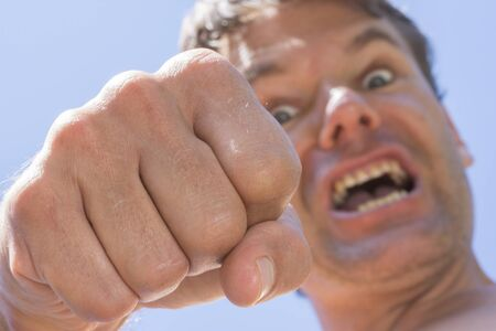 upward struggle: Closeup low angle of vicious angry Caucasian man throwing punch down at camera with sunny blue sky background