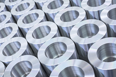 precision: Closeup pattern of shiny circular precision stainless steel industrial machine parts arranged in rows
