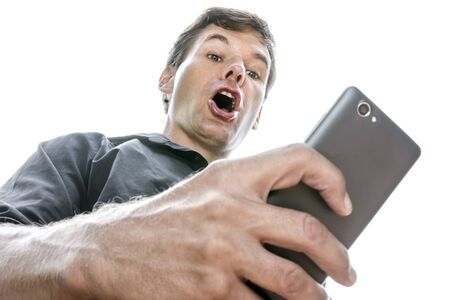 down: Low angle closeup Caucasian man looking down at his cell phone shows expression of shock as he opens his mouth in disbelief on white background