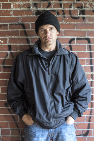Caucasian man with serious expression wears hoodie, jacket and jeans and leans against brick wall with graffiti in urban setting with hands in pockets