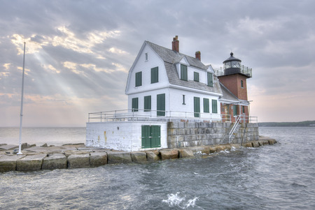 high tide: HDR image of Rockland Harbor Breakwater Lighthouse at high tide under cloudy sky with rays of sunlight shining down on ocean in Maine