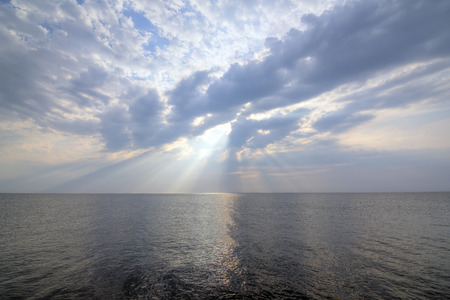 Beautiful calm ocean with glorious sky and rays of sunlight shining down through gray clouds of heaven