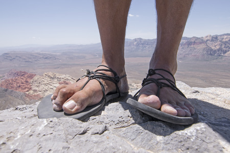 Closeup of weathered worn male feet and toes in primitive simple sandals with black laces standing on top of rocky mountain overlooking Red Rock Canyon desert in Nevada Standard-Bild