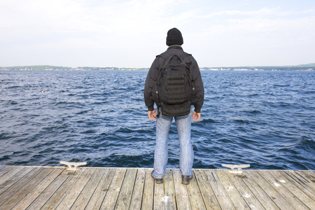 inlet bay: Back side of man with black backpack and jacket standing at end of wooden dock overlooking choppy waters of bay in Rockland Maine Stock Photo